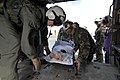 US Navy 070701-N-0194K-046 Aviation Warfare Systems Operator 2nd Class Trevor Ahrendt, from Helicopter Sea Combat Squadron (HSC) 28, assists Air Force Tech. Sgt. Michael Cooper as they place a Guatemalan patient onto an MH-60S.jpg