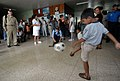 US Navy 070719-N-0194K-201 A local boy passes a soccer ball to Capt. Bob Kapcio, mission commander aboard the Military Sealift Command hospital ship USNS Comfort (T-AH 20), during a tour of Jose Schendal Health Center.jpg