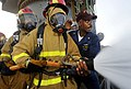 US Navy 090917-N-5345W-013 Chief Hull Maintenance Technician Jeffrey Middleton, right, trains fire team members on how to properly relieve the nozzleman during a general quarters drill.jpg