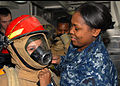 US Navy 091221-N-9643W-421 Damage Controlman 2nd Class Tiffany Epps, a member of the damage control team helps a child from the Virginia Home for Boys and Girls (VHBG) don the full fire fighting ensemble.jpg