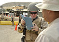 US Navy 110717-N-NX238-015 Master-at-Arms 3rd Class Chad Crow inspects identification papers at a check point while conducting force protection tra.jpg