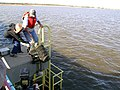US Navy 111006-N-ZZ999-001 Dr. Beth Ravitt, from Rutgers University, left, and Frank Steimle drop oyster cages into Raritan Bay from the Naval Weap.jpg