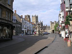 Wells, Somerset - The Market Place is the site of one of the city's ancient wells (note the water flowing in the gully, down High Street); the Bishop's Eye gatehouse (to the Bishop's Palace) is at the far end; two of Wells Cathedral's towers can be seen rising behind the buildings.