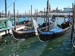 Several gondolas docked in Venice.