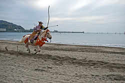 Mounted archer rides on beach.