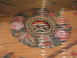 Harpsichord - Detail of the harpsichord by Karl Conrad Fleisher; Hamburg, 1720 in Museu de la Música de Barcelona. A decorative rose descends below the soundboard in which is it mounted; the soundboard itself is adorned with floral painting around the rose. The bridge is at lower right.