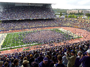 Washington Huskies football - Ecstatic Huskies fans storm the field in celebration after defeating the heavily favored No. 3 USC Trojans in an upset.