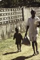 ASC Leiden - F. van der Kraaij Collection - 02 - 026 - A smiling man carrying a bread and a child on a dirt road near a wall - continued - Old Road, Monrovia, Montserrado County, Liberia, 1977.tiff