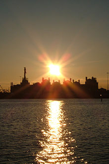 Sunset behind cluster of buildings, with water in foreground
