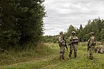 A Soldier from Task Force Baltic Phoenix, 3-10 General Support Aviation Battalion, 10th Combat Aviation Brigade, pulls security with Soldiers from the Latvian National Guard.jpg
