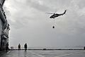 A U.S. Navy MH-60S Seahawk helicopter assigned to Helicopter Sea Combat Squadron (HSC) 25 transports a pallet of water from the dry cargo and ammunition ship USNS Charles Drew (T-AKE 10) in the Philippine Sea to 131114-N-ZT599-030.jpg