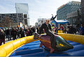A U.S. Sailor assigned to the amphibious transport dock ship Pre-Commissioning Unit (PCU) Anchorage (LPD 23) rides a mechanical salmon at the Dock on the Block party in downtown Anchorage, Alaska, April 30 130430-N-DR144-057.jpg