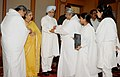 A group of Brahmkumari tying 'Rakhi' to the Prime Minister, Dr. Manmohan Singh, on the occasion of 'Raksha Bandhan', in New Delhi on August 13, 2011. Smt. Gursharan Kaur is also seen.jpg