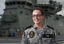 Eine Frau, die eine getarnte Militaruniform auf dem Deck eines Schiffes tragt