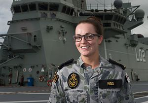 A woman wearing a camouflaged military uniform on the deck of a ship