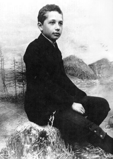Studio photo of a boy seated in a relaxed posture and wearing a suit, posed in front of a backdrop of scenery.