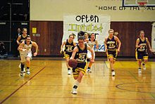A female high school basketball player dribbles the ball towards the camera with a focused look on her face. Behind her trail basketball members from her team and the opposing team. All are running towards the camera.