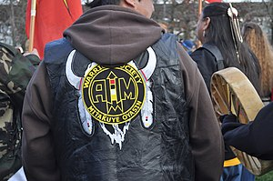 American Indian Movement - A member of the Warrior Society Mitakuye Oyasin wears an AIM jacket at the raising of the John T. Williams Memorial Totem Pole, Seattle Center