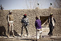 An interpreter and Afghan Border Police Pvt. Ghul Faruq, a medic with 2nd Tolai, 2nd Kandak, Helmand ABP, speak with a local boy while fellow ABP search a compound during a partnered security patrol with U.S 120130-M-MM918-005.jpg