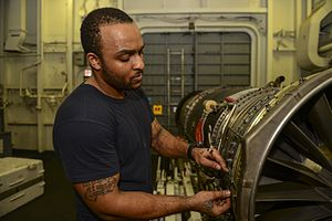 Aviation machinist's mate - An aviation machinist's mate performs maintenance on a jet engine in the jet shop of an aircraft carrier.