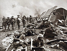 Injured soldiers lie amongst debris while others walk past nearby