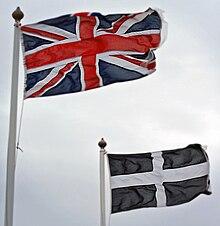 La Unio kaj kornvalaj flagoj flugetantaj en la vento, kontraŭ griza, nuba ĉielo.
