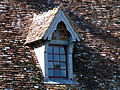 Chien assis - toit d'une ferme du château.JPG