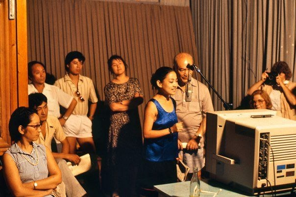 Chinese actors dubbing a television show as others look on 1987