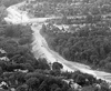 A black and white photo taken from the air, showing the progress on a road under construction through a forested valley