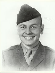A young man dressed in his military uniform and wearing a Marine Corps style hat. He is smiling.