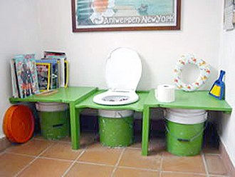Bucket toilet - Bucket toilet with spare buckets stored on either side.
