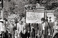 "A protest march, with a sign ""No More Birminghams"" prominent. Some of the marchers are black and some are white; all are well-dressed."