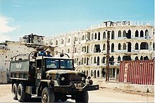 Military truck in front of building