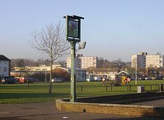 A photograph of an urban park with houses and flats in the distance. The park large, and mostly grass. A football goal is in the centre of the park, and a pub sign is in the foreground.