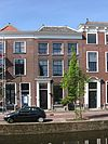 foto van Pand van twee verdiepingen met eenvoudige lijstgevel waarin boven de oorspronkelijke schuiframen