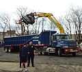 Demolition lifting burnt car to waste removal truck.JPG