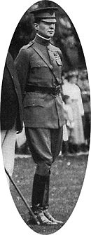 Man wearing peaked cap, Sam Browne belt, and shiny riding boots.