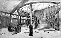 View of a wide branching staircase, leading off to the left and right top of the scene. Elaborate balustrades line the steps, down which a woman is walking. At the head of the stairs a wall clock is visible, and above that a segmented dome. A man and a woman sit in chairs in the foreground.