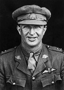 Half portrait of man in military uniform with peaked cap and pilot's wings on chest