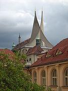 La toiture moderne de béton gris d'un édifice ancien, en forme de deux pointes entrelacées et pointées vers le ciel.