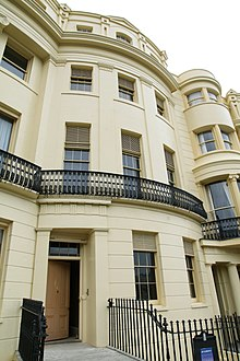 A cream coloured terrace house built in Regency style. It has 5 floors and the photo shows the house from street view. There are black cast iron railings in front of the building and the building has a basement which you can just about see in the photo.