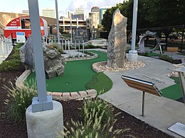 A miniature golf course with putting greens with art installations such as rock formations and brightly-painted guitars