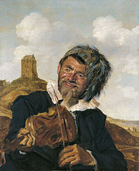 Left-handed violin player in a dune landscape