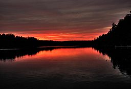 Red, yellow, and purple clouds are reflected in a lake surrounded by silhouetted trees.