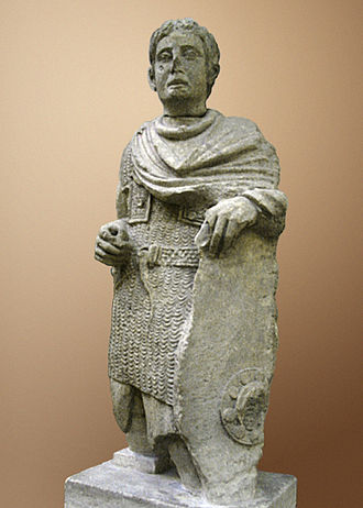 Gallo-Roman culture - A Gallic warrior dressed in Roman lorica hamata (chainmail) with a cloak over it whilst wearing a torc around his neck; he also wields a Celtic-style shield, although the proportions of the body and overall realism are more in line with Classical and Roman art than with Celtic depictions of soldiers.