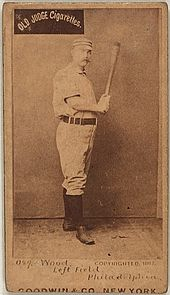 A sepia-toned baseball card image of a man wearing an old-style white baseball uniform and cap and holding a baseball bat