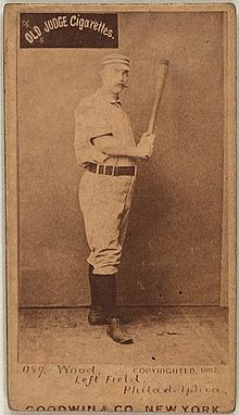 A sepia-toned baseball card image of a man wearing an old-style white baseball uniform and pillbox cap holding a baseball bat with both hands