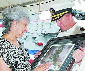 Alfredo Cantu Gonzalez - Dolia Gonzalez accepts a painting of her son from Commander Brian Fort during a change of command ceremony for the USS Gonzalez in 2009