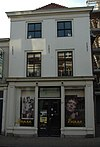 foto van Hoekpand (naast R.K.Kerk). Pand met schilddak, aan de achterzijde afgesloten door een puntgevel. Gepleisterde lijstgevel met schuiframen in de verdiepingen. Zijgevel modern