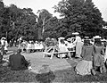 Group of children seated at tables and some kneeling, possibly a children's party or festival. (22325999786).jpg